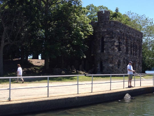 Frank Whelan fished while his wife, Cathy Whelan, searched for a money-filled envelope hidden in Glen Island Park in New Rochelle on Monday. The envelope, stuffed with $50, was later found between two rocks near the castle. It was placed there as part of a Twitter-based phenomenon known as Hidden Cash.