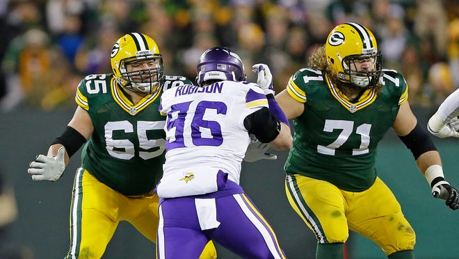 Green Bay Packers guards Lane Taylor (65) and Josh Sitton (71) block Minnesota Vikings defensive end Brian Robison (96) at Lambeau Field. Sitton played left tackle in the game with David Bakhtiari out.