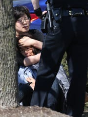 A woman is consoled following a March 30, 2014, shooting at a clothing store in a strip mall at 38th and Rural streets, Indianapolis. The woman came out of the store where the shooting occurred.