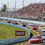 A pack of NASCAR Sprint Cup Series cars race into Turn 2 during the Cheez-It 355 at Watkins Glen International.