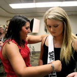 Mississippi Miss Hospitality board member Kristen Brock helps Courtney Blount of Sumrall with her sash during check-in at the University of Southern Mississippi.