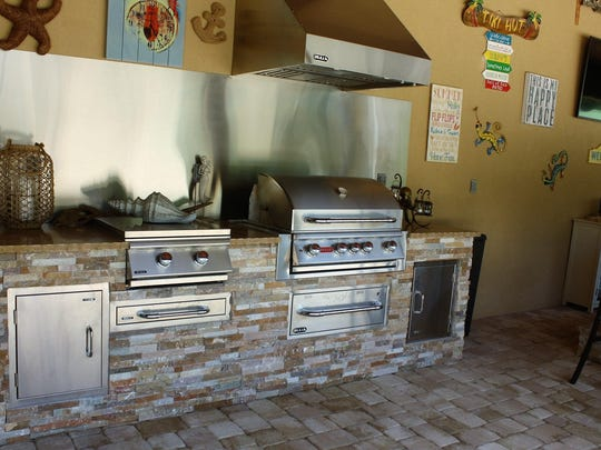 The Vickers' outdoor dining area features a stainless outdoor kitchen with undercounter refrigerator, ice machine, sinks and food preparation areas.