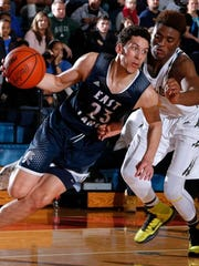 East Lansing's Brandon Johns, left, drives against