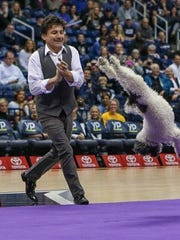Richard Olate applauds a back flip by one of his dogs