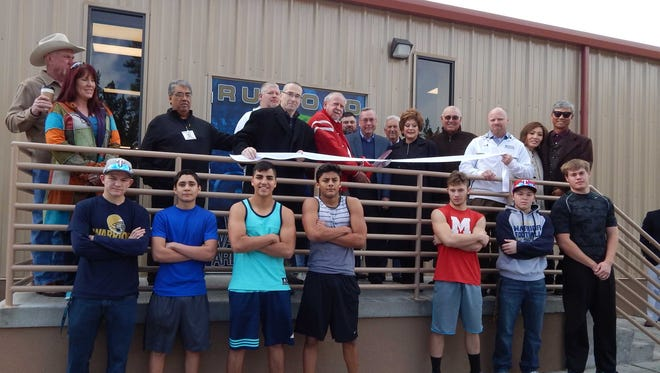 R.D and Joan Dale Hubbard help Ruidoso High School board members, staff and athletes cut the ribbon Monday for the school's new Hubbard-Warrior Weight Room.