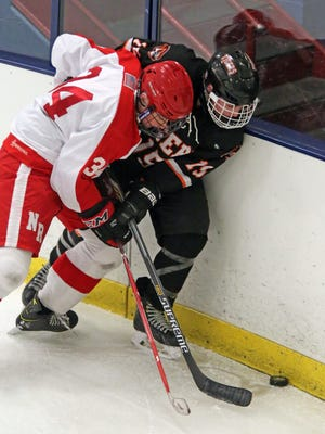 North Rockland's John Gomley (34) and Ethan Klipstein (15) of White Plains fight for control of the puck during hockey game at Sport O-Rama Ice Rink in Monsey Jan. 27, 2016. North Rockland defeated White Plains 3-1.