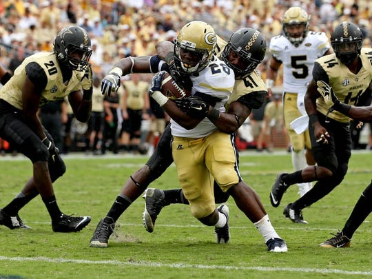 Georgia Tech running back Dedrick Mills (26) scores against Vanderbilt  linebacker Zach Cunningham (41) in the third quarter last season.
