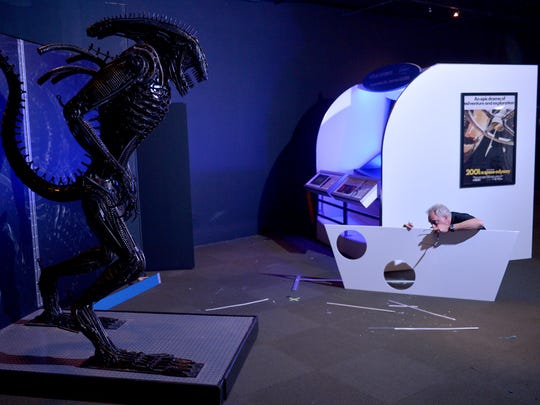 "Eric Warp, with Stage Nine Exhibitions, assembles a panel next to an alien sculpture on display in ""Interactive! The Exhibition"" at the Ronald Reagan Presidential Library & Museum in Simi Valley on Thursday."