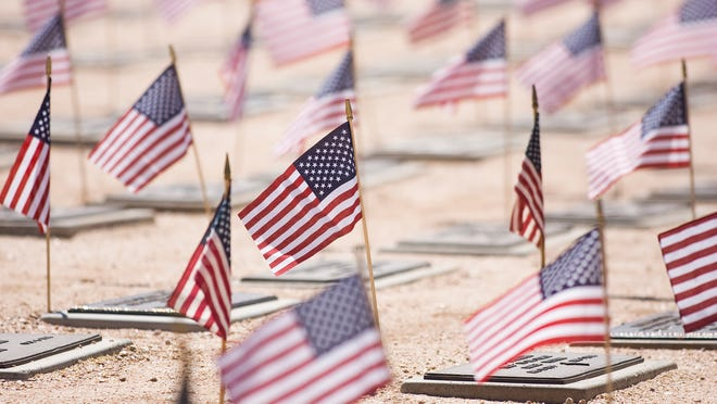 Flags wave over grave markers during Memorial Day ceremonies at the National Memorial Cemetery of Arizona in Phoenix, Monday, 5-31-2010.