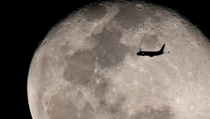 An airplane flies against the backdrop of the rising moon after taking off from Miami International Airport on Feb. 13, 2017.