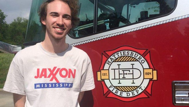 Cody Bass of Brandon stands next to a Hattiesurg fire truck with his logo design.