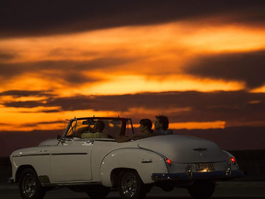 Tourists ride a vintage American convertible during
