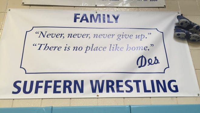 A banner hangs in tribute to late wrestling coach Mickey DeSimone in Suffern High School's wrestling room.