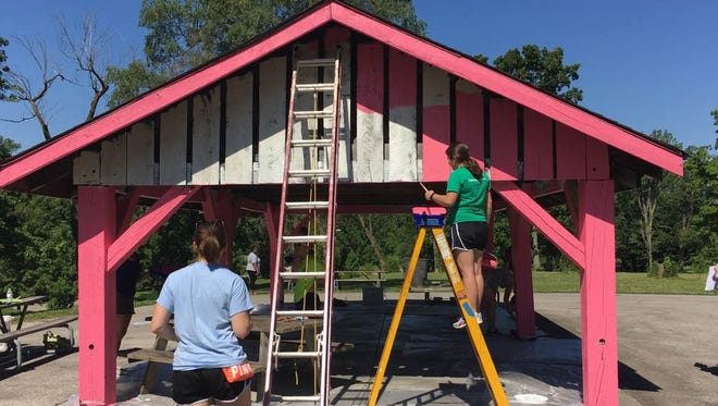 """Volunteers paint one of the shelters at McCulloch Park during the Paint the Park event Saturday, June 25. The event was part of the Whitely Community Council's """"Year in Color"""" beautification campaign."""