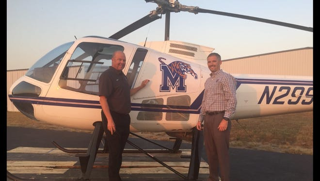 Memphis football coach Mike Norvell, right, and running backs coach Darrell Dickey prepare to board a helicopter during a night of recruiting on October 7, 2016.