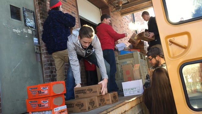 """South Western School District students unpack donations collected for a """"Stuff the Bus"""" food drive for New Home Ministries in Hanover."""