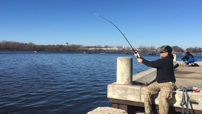 Mark Bunchek of Green Bay takes advantage of the unseasonably warm temperatures, fishing Tuesday on the Fox River at Voyageur Park in De Pere.