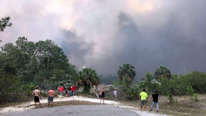 Residents stand watching the emergency crews Friday, April 21, 2017, head into and out of the dark cloud of smoke.