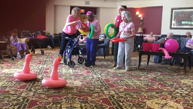 Residents at Spring Hills play Flamingo Ring Toss to celebrate National Pink Day.
