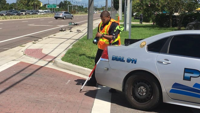 A Rockledge police officer prepares equipment used in a traffic homicide investigation Tuesday on U.S. 1.