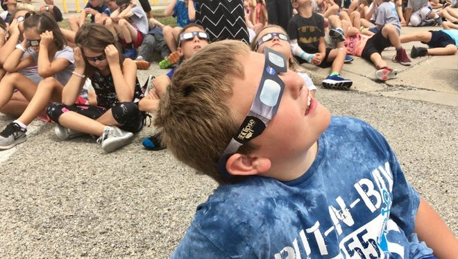 Third-grader Grayson Horchner looks up at the partial eclipse Monday afternoon outside Maple Glen Elementary School in Westfield Monday, Aug. 21, 2017.