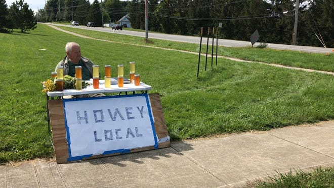 """Mike Shtengrat is known by Webster residents as the """"Honey Man."""" His handwritten sign uses a Ukrainian letter in place of the N"""