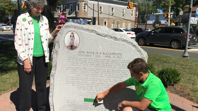 Rosemarie D'Alessandro looks on as Michael Kazigian, 13, of Washington Township on Sat., Sept. 23, 2017, unveils the newest engraving on the White Butterfly Sculpture, which was erected in her daughter's memory. The engraving marks the date that lawmakers unanimously passed a bill that would amend Joan's Law, named after D'Alessandro's daughter.