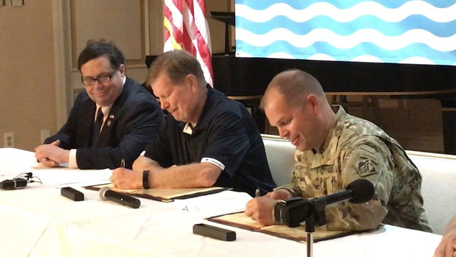 John LaRue (center), executive director of the Port of Corpus Christi, and U.S. Army Corps of Engineers-Galveston District Commanding Officer Col. Lars Zetterstrom (right) sign a Project Partnership Agreement for expansion of the Corpus Christi Ship Channel on Friday. The deal capped a 27-year effort to expand the ship channel.