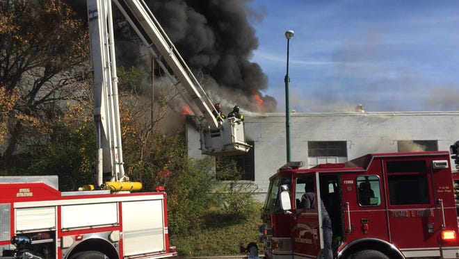 Firefighters work to put out a fire at a towing company on South Main on Monday.