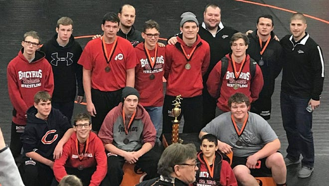 The Bucyrus wrestlers pose with their medals and the invitational trophy.