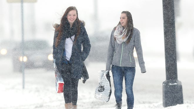 Taylin St. Mary, left, and Hailey Rose of Eden brave the snow Tuesday to shop at Forest Mall.