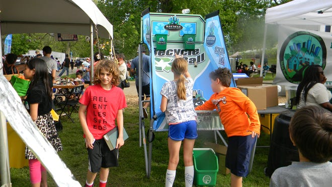 Festival-goers enjoy a recycling game at a past Earth Day festival.