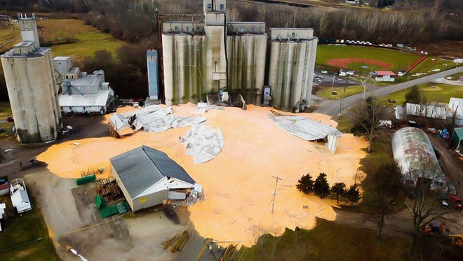 Thousands of bushels of corn cover Ohio Route 571 Monday, Jan. 22, 2018 after a grain bin at Miami Valley Feed and Grain collapsed on Sunday evening in New Carlisle, Ohio. Emergency personnel were still assessing the scene Monday morning. (Jared Thrush/Dayton Daily News via AP)