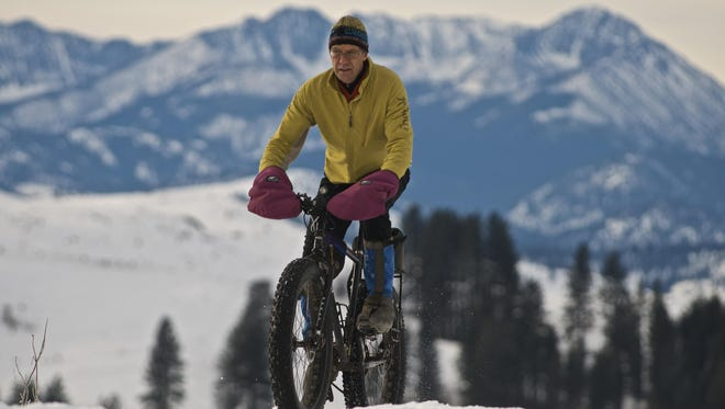 Steve Mitchell, another Trail Volunteer, on his bike with peaks in the Chelan-Sawtooth Wilderness in the background.