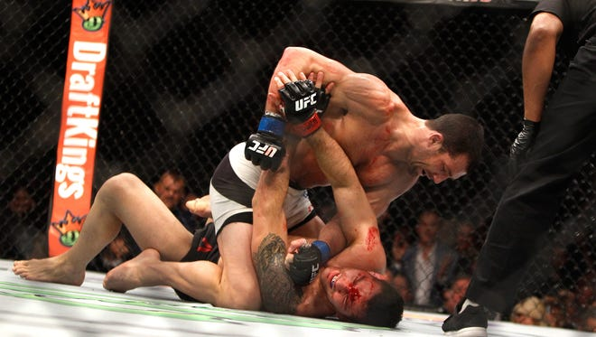 Luke Rockhold (top) punches Chris Weidman in their middleweight title fight during UFC 194 on Saturday in Las Vegas. Rockhold took the title with a fourth-round TKO.