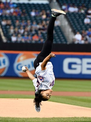 Olympic gold medalist Laurie Hernandez performs flips from the mound before throwing out the ceremonial first pitch before the baseball game between the New York Mets and the Washington Nationals, Saturday, Sept. 3, 2016, in New York.