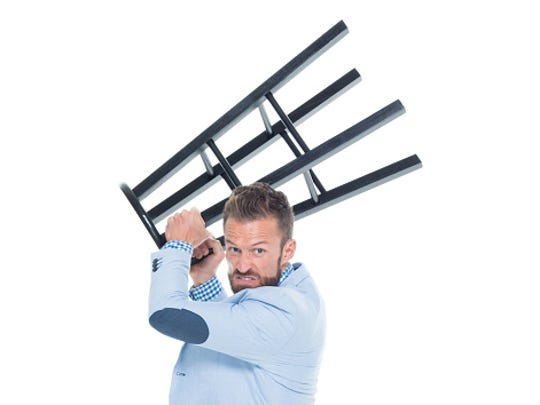 Angry businessman throwing stool