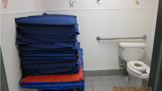 One example of the 36 violations, children's sleeping mats with sheets already on them were found stored in the children's bathroom next to the toilet.