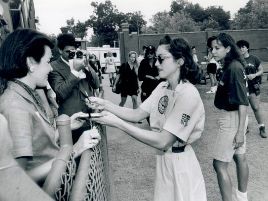 Madonna, right, signs autographs for members of the
