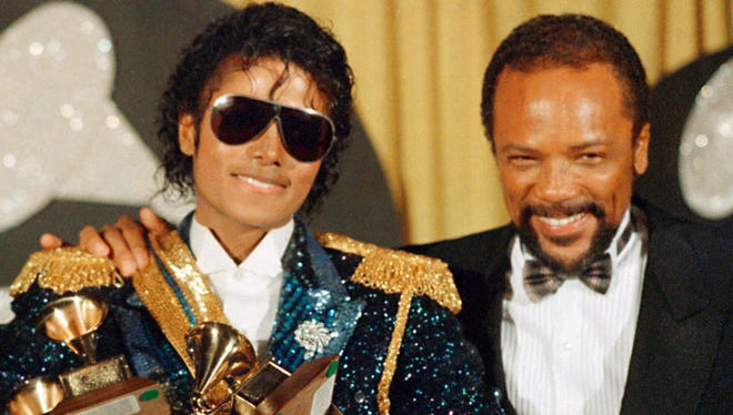 In this Feb. 28,1984, photo, Michael Jackson, left, holds eight awards as he poses with Quincy Jones at the Grammy Awards in Los Angeles.