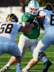 Novi lineman Adam Guirey (middle) takes on two Hartland