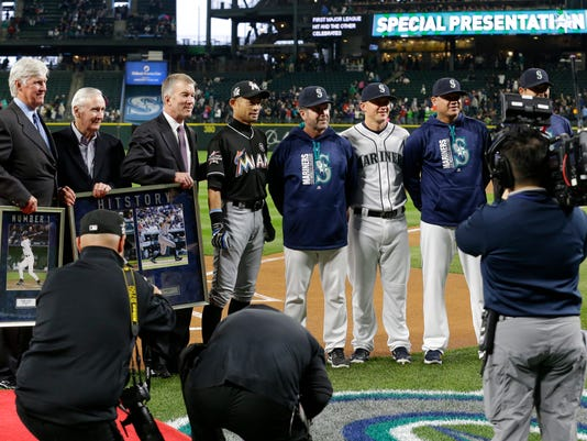 Miami Marlins' Ichiro Suzuki, fourth from left, is honored by Seattle Mariners players and executives for his 3,000 hit milestone in a pre-game ceremony before a baseball game against the Mariners, his former team, Monday, April 17, 2017, in Seattle. (AP Photo/Ted S. Warren)