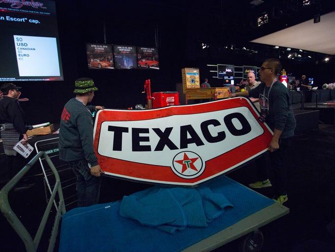 Barrett-Jackson employees lift a Texaco Oil service