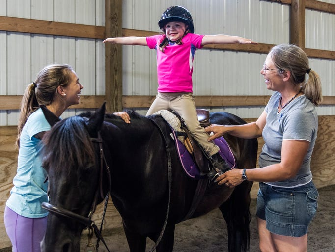Kinsley Jenkin (center), 4, uses her leg muscles to
