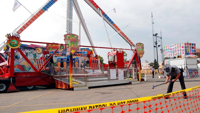 In this July 27, 2017 file photo, an Ohio State Highway Patrol trooper removes a ground spike in front of the Fire Ball ride at the Ohio State Fair, in Columbus, Ohio. Attorneys for the family of a teenager killed in a thrill ride accident at the Ohio State Fair and others left with life-changing injuries believe the state's inspectors missed obvious warning signs. But the attorneys won't include the state in any lawsuits or financial settlements because Ohio, like many other states, gives its carnival ride inspectors immunity from accusations of negligence.