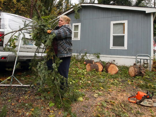 Neighbors Sherree and Dale Thorp help clean debris from the home on Arnold Avenue in Port Orchard where a 15-year-old girl was injured by a falling tree on Monday. The girl remained hospitalized Tuesday afternoon.