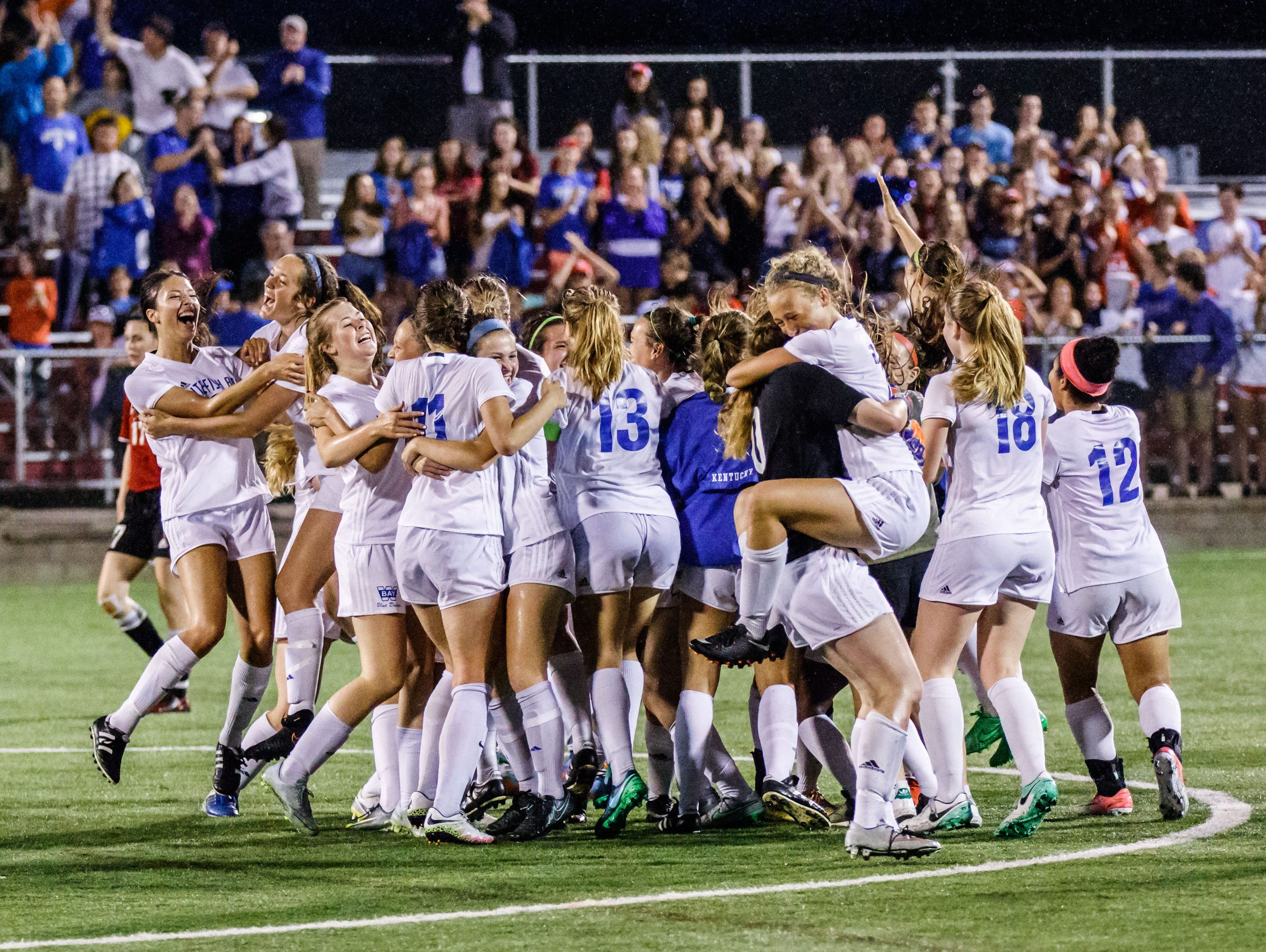 Whitefish Bay players celebrate after winning the WIAA