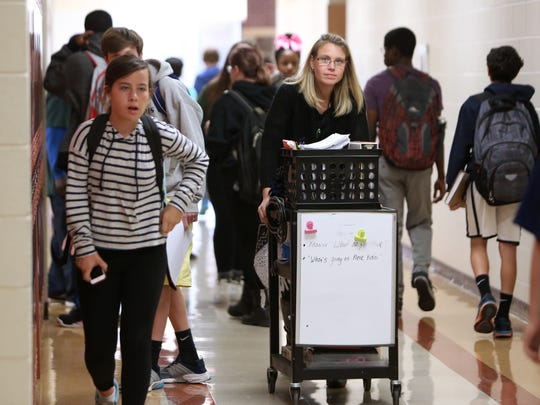 Susan Macsotai, a science teacher at Walnut Hills, pushes a cart down the hall to get to her next class on October 14. Several teachers at the school are considered 'floating' meaning they don't have a classroom of their own.