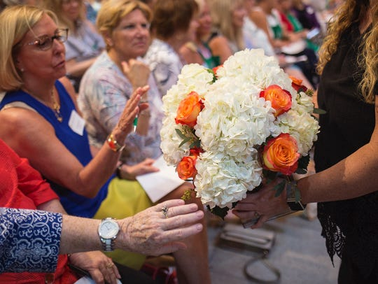 Attendees inspect an arrangement made by designer Michael