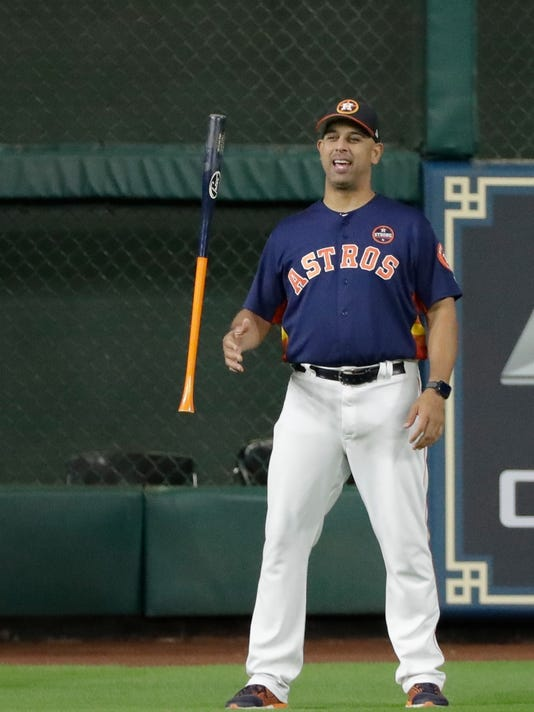 Houston Astros bench coach Alex Cora flips a bat before Game 6 of the American League Championship Series baseball game against the New York Yankees Friday, Oct. 20, 2017, in Houston. (AP Photo/David J. Phillip)